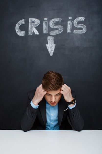 Maschera dell'uomo stanco sopra la lavagna con l'iscrizione di crisi Foto Gratuite
