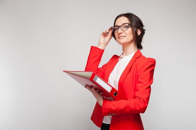 Maschera di bella donna in giacca rossa che sta con i documenti in mani Foto Premium