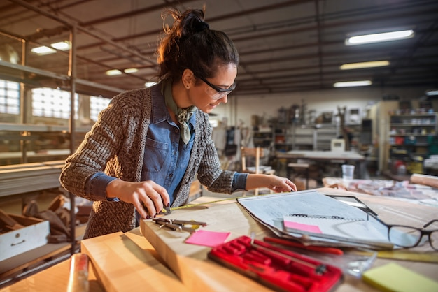 Maschera di bello architetto focalizzato della donna di mezza età nella sua officina che lavora ai nuovi progetti. Foto Premium