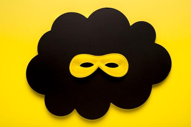 Maschera di carnevale giallo vista dall'alto sulla nuvola di carta nera Foto Gratuite