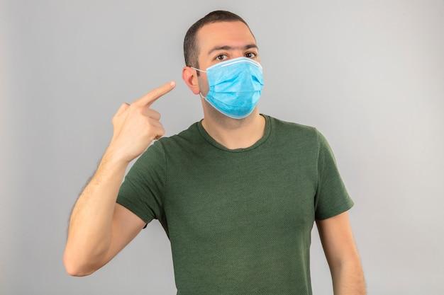 Maschera medica da portare del fronte del giovane che indica se stesso con la barretta su bianco isolata Foto Gratuite