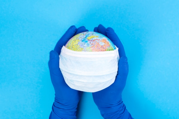 Maschera medica monouso sul globo nelle mani di un medico, modello della terra. il concetto di una pandemia. kovid-19, coronavirus. l'epidemia globale della malattia. Foto Premium