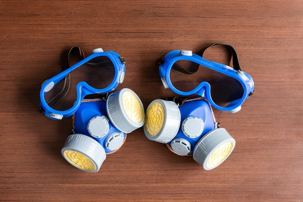 Maschera respiratoria, maschera antipolvere e maschera di sicurezza per prodotti chimici industriali su fondo di legno. Foto Premium