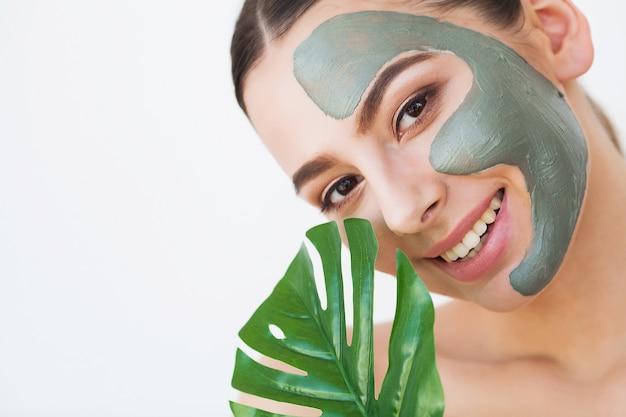 Maschera viso. bella donna sorridente che applica maschera sul viso Foto Premium