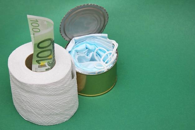 Maschere mediche in una lattina accanto a un rotolo di carta igienica e una fattura da 100 euro. Foto Premium