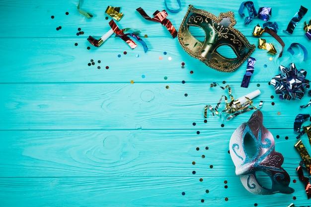 Mascherina di carnevale di travestimento due con i coriandoli sopra la tabella blu Foto Gratuite