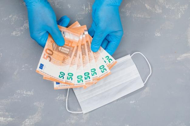 Mascherina medica sul tavolo in gesso e mani che tengono le banconote. Foto Gratuite