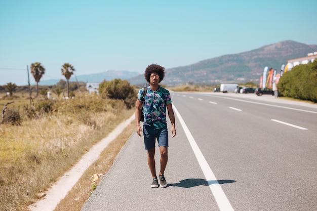 Maschio afroamericano che cammina sul bordo della strada Foto Gratuite