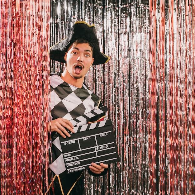 Maschio allegro con l'ardesia di film alla festa di carnevale Foto Gratuite