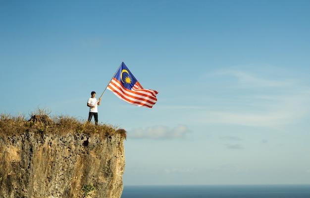 Maschio asiatico con la bandiera indonesiana che celebra la festa dell'indipendenza Foto Premium