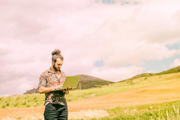 Maschio barbuto che lavora al computer portatile in campagna Foto Gratuite