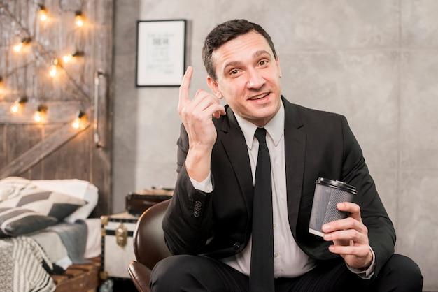 Maschio carismatico che pondera tenendo la tazza di caffè in mano Foto Gratuite