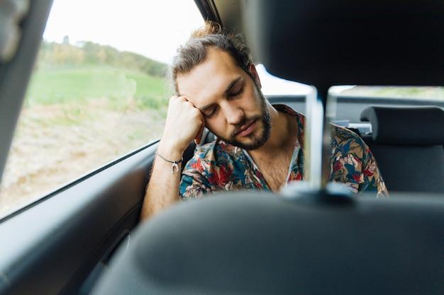 Maschio che dorme nel sedile posteriore della macchina Foto Gratuite