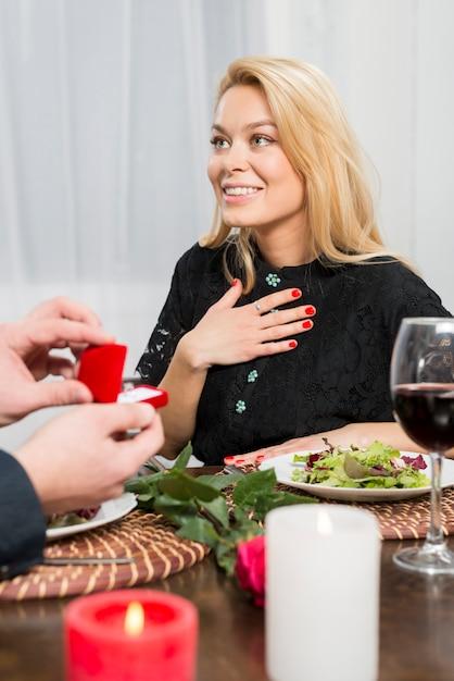 Maschio che presenta il contenitore di regalo con l'anello alla femmina sorpresa alla tavola Foto Gratuite