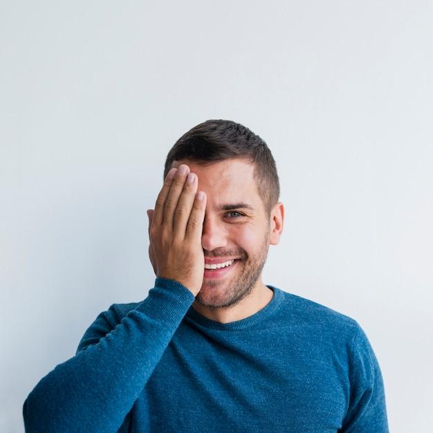 Maschio che sorride e che copre mezza faccia con una mano Foto Gratuite