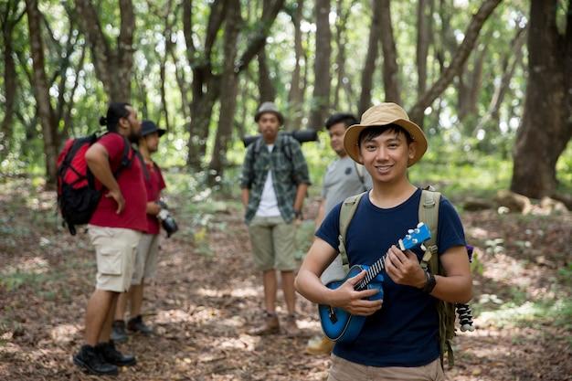 Maschio con le ukulele che fanno un'escursione alla foresta Foto Premium