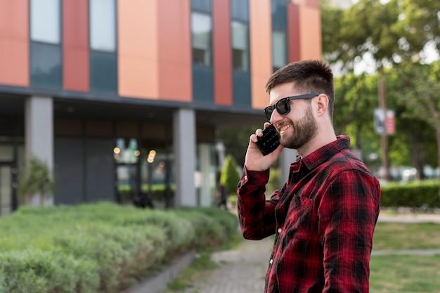 Maschio con occhiali da sole parlando su smartphone Foto Gratuite
