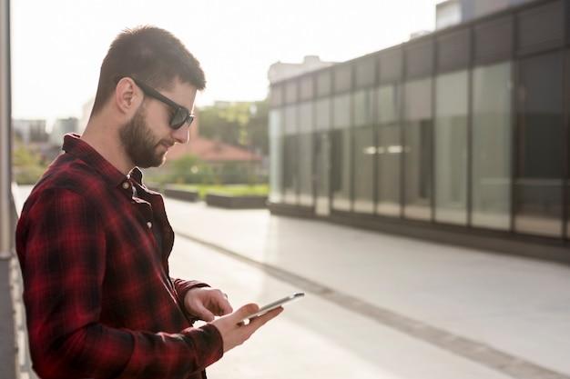 Maschio con occhiali da sole usando smartphone Foto Gratuite