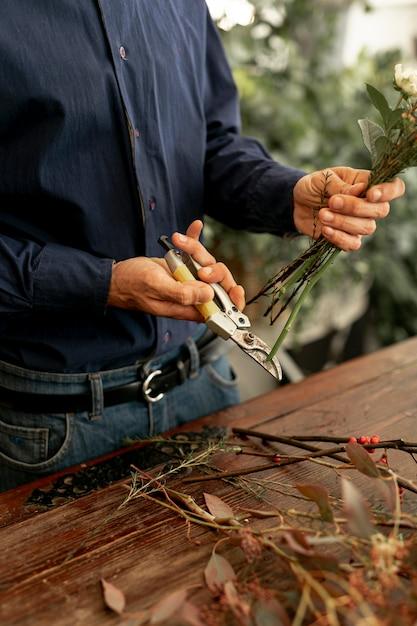 Maschio del fiorista che taglia i gambi del fiore Foto Gratuite