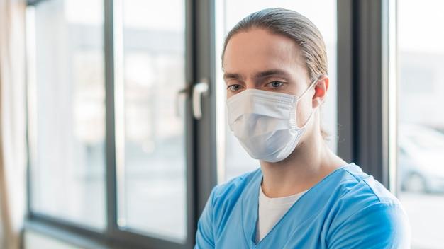 Maschio dell'infermiera dell'angolo alto con la mascherina medica Foto Gratuite