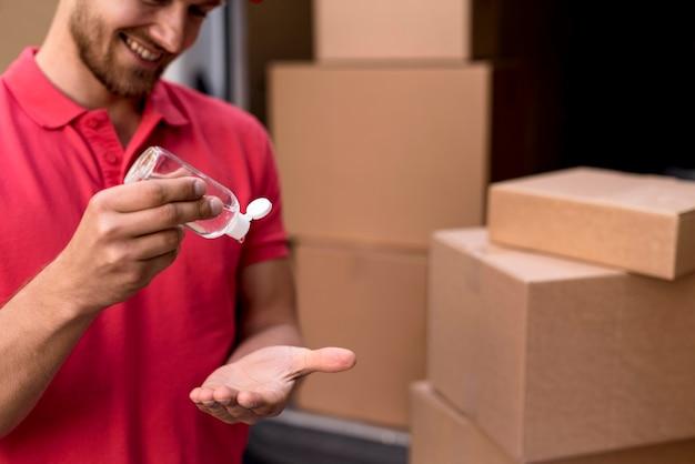 Maschio di consegna del primo piano che usando disinfettante per le mani Foto Gratuite