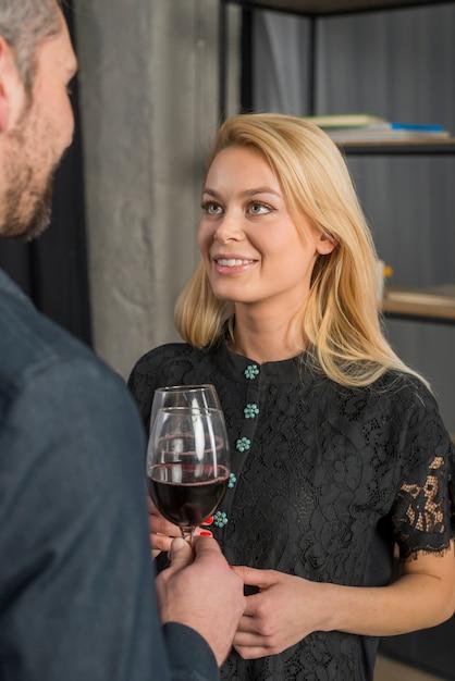 Maschio e felice femmina clanging bicchieri di vino in camera Foto Gratuite