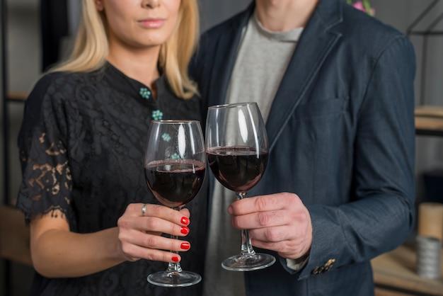 Maschio e femmina con bicchieri di vino in camera Foto Gratuite