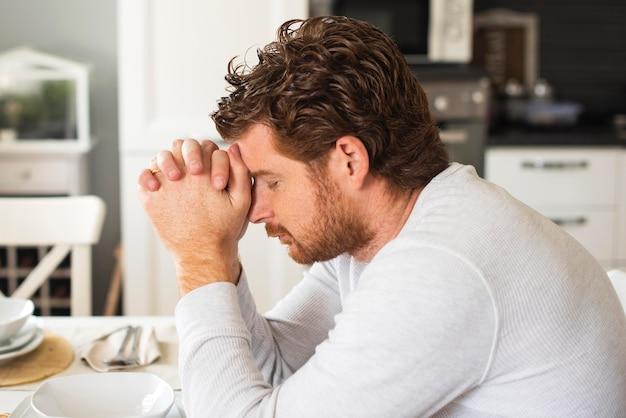 Maschio emozionale adulto che prega a casa Foto Gratuite