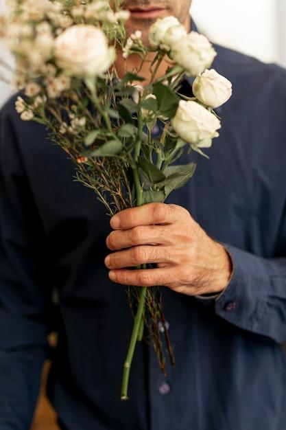 Maschio fiorista in possesso di un bellissimo mazzo di fiori Foto Gratuite