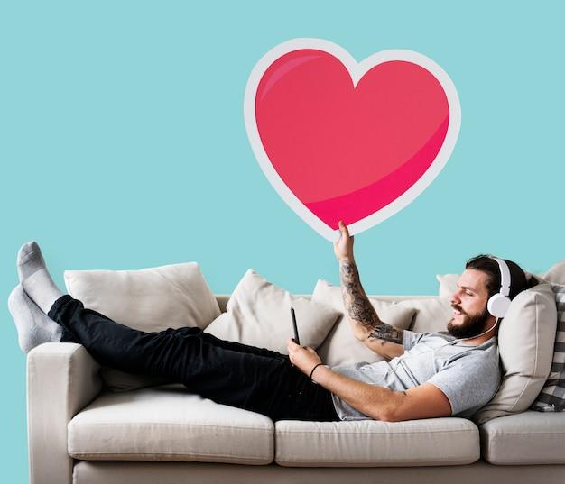 Maschio su uno strato che tiene un'emoticon del cuore Foto Gratuite