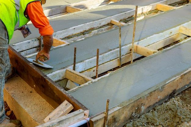 Mason che costruisce un cemento del massetto ai lavori del pavimento. versando la pavimentazione in calcestruzzo Foto Premium