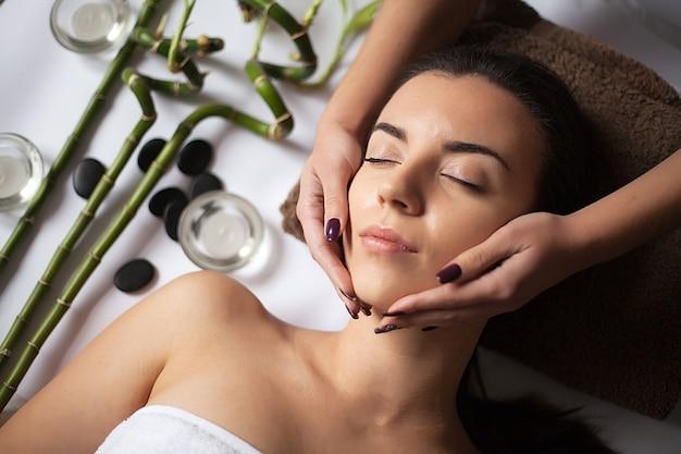 Massaggiatore che fa massaggio sul corpo della donna nel salone della stazione termale. Foto Premium