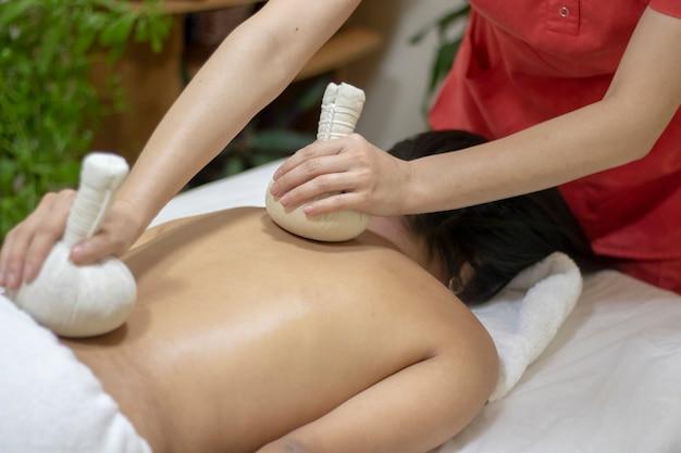 Massaggiatore facendo massaggio sul corpo della donna nel salone spa Foto Premium