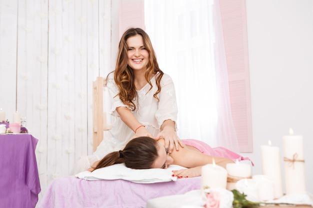 Massaggiatore femminile che fa massaggio sulla parte posteriore della donna sulla stazione termale Foto Gratuite