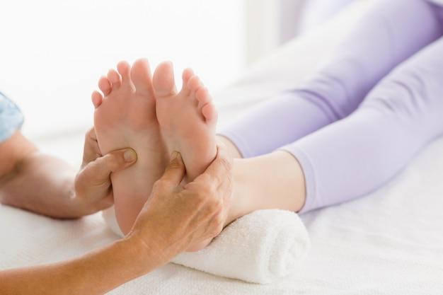 Massaggiatore ritagliato che dà massaggio ai piedi alla donna Foto Premium