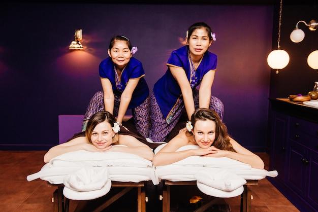 Massaggiatori tailandesi in abiti etnici rendono le tradizionali procedure spa per belle donne felici Foto Premium