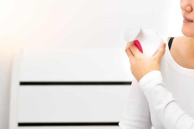 Massaggiatrice elettrica con collo e spalle sulle spalle delle donne Foto Premium