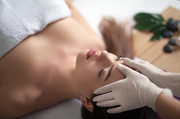 Massaggio al viso. primo piano di una giovane donna che ottiene trattamento della stazione termale. Foto Premium