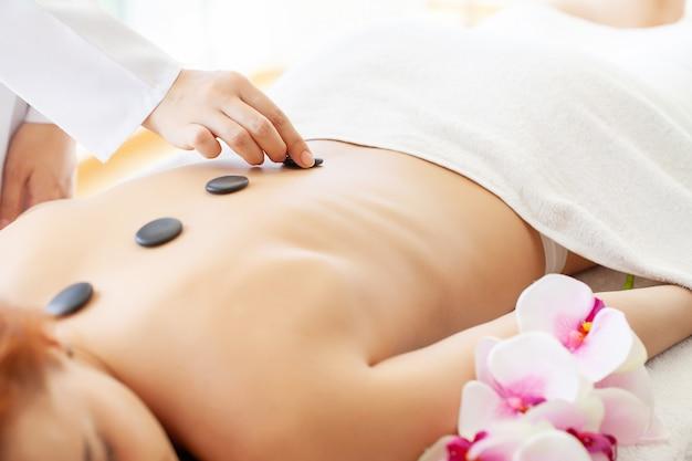 Massaggio con pietre spa, bella donna che ottiene massaggio con pietre calde spa nel salone spa Foto Premium
