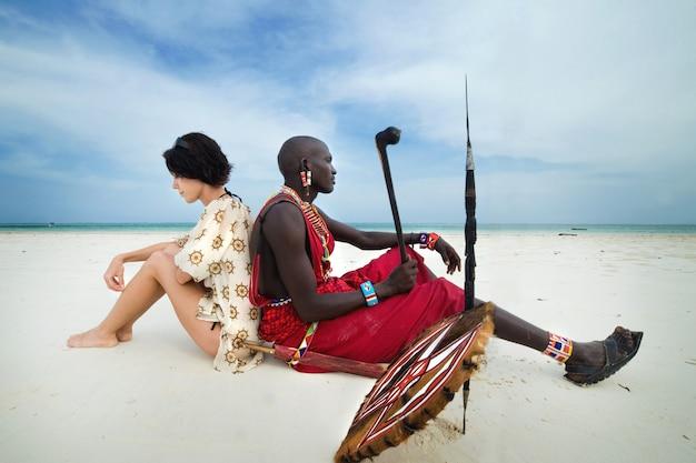Massai e donna bianca sulla spiaggia Foto Premium