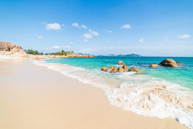 Massi di roccia unici dell'acqua trasparente turchese tropicale splendida della spiaggia, destinazione di viaggio della costa sud-orientale di cam ranh nha trang Foto Premium