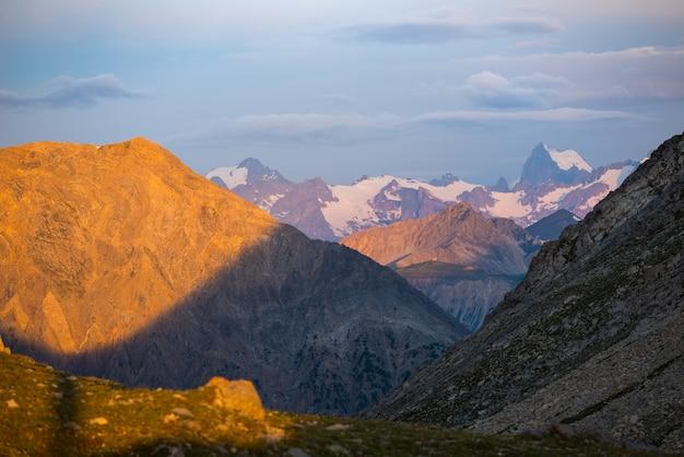 Massif des ecrins france. cielo colorato all'alba, maestose vette e ghiacciai, paesaggio drammatico. Foto Premium