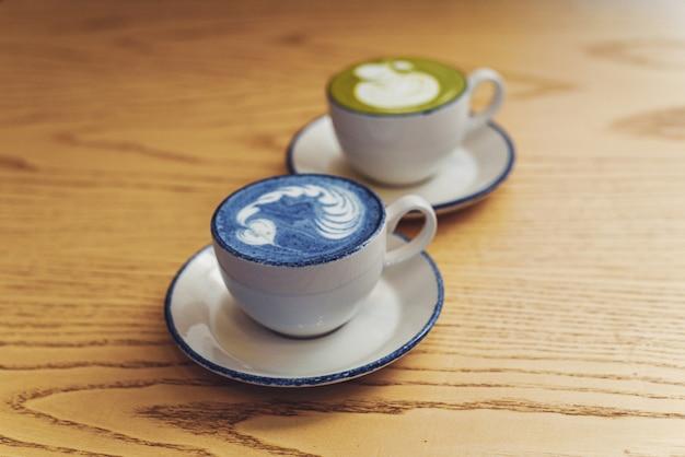 Matcha blu e verde in tazze bianche ceramiche su una tavola di legno con copyspace Foto Premium