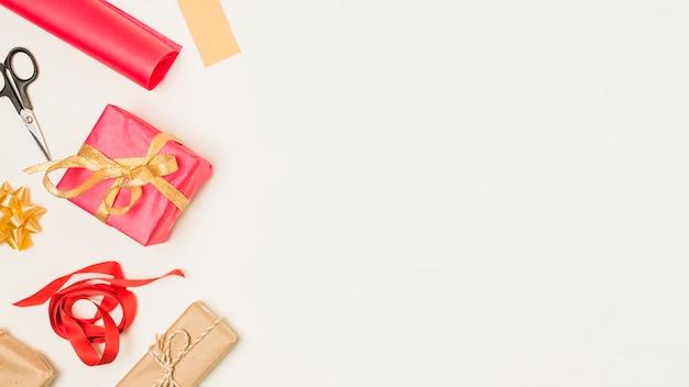 Materiale per confezioni regalo e regali disposti sul lato dello sfondo Foto Gratuite