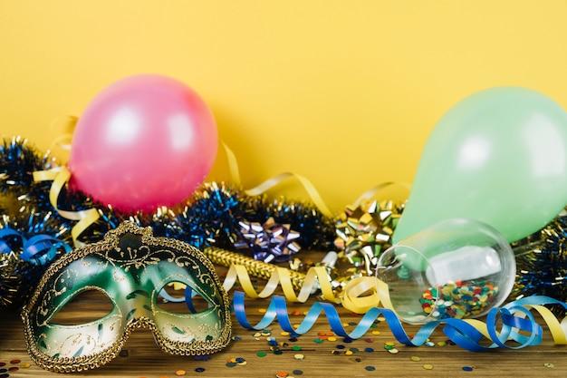 Materiale per la decorazione del partito con maschera di piume di carnevale mascherata e palloncini sulla tavola di legno Foto Gratuite