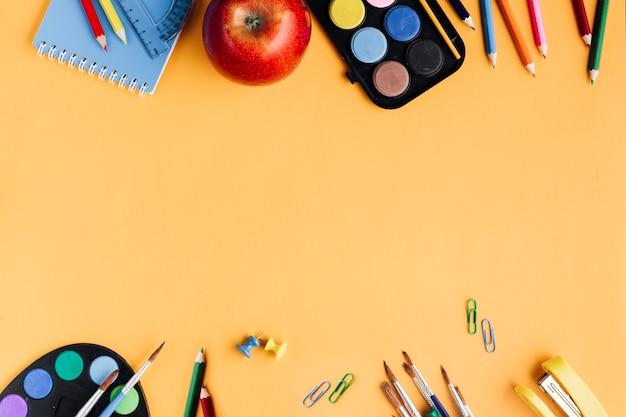 Materiale scolastico colorato posto su sfondo giallo Foto Gratuite