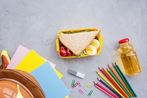 Materiale scolastico e lunch box con sandwich e verdure Foto Premium