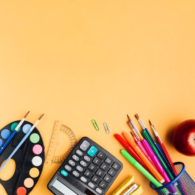 Materiale scolastico multicolore e mela rossa sparsi sulla scrivania gialla Foto Gratuite