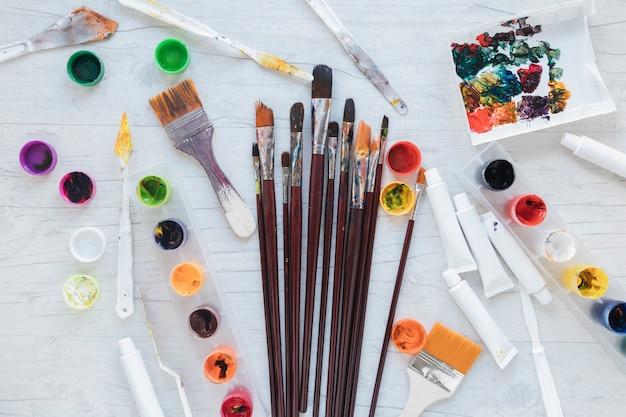 Materiali artistici sparsi sul tavolo bianco dall'alto Foto Gratuite