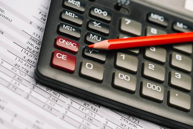 Matita colorata rossa sul calcolatore sopra il rapporto finanziario Foto Gratuite